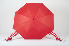 The girl hiding behind a large red umbrella Stock Photos