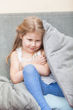 Girl hiding behind a pillow on the sofa Stock Image