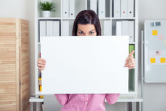 Girl hiding behind a sheet of paper Royalty Free Stock Images