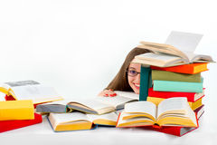 Girl hiding behind stack of colorful books. And smiling Royalty Free Stock Image