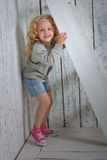 Girl hiding behind the stairs. Little girl hiding behind the stairs Royalty Free Stock Image