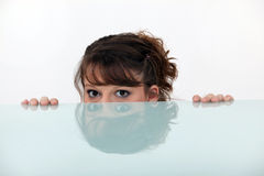 Girl hiding behind a table, Royalty Free Stock Photo