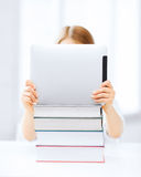 Girl hiding behind tablet pc and books at school Royalty Free Stock Photos