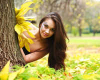 Girl hiding behind a tree. Pretty smiling girl hiding behind a tree in the autumn park Stock Photography