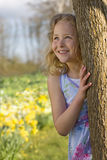 Girl hiding behind tree Stock Images