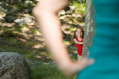 Girl hiding behind a tree Royalty Free Stock Photo