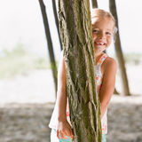 Girl hiding behind tree Royalty Free Stock Images