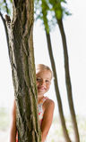 Girl hiding behind tree stock photography
