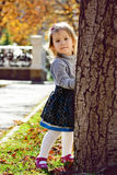 Girl hiding behind the tree Royalty Free Stock Photo