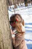 Girl hiding behind the trees Royalty Free Stock Images