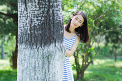 Girl hiding behind the trees Royalty Free Stock Photos