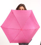 Girl hiding behind umbrella Stock Image