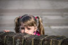 Girl hiding behind a wall. Cute little Caucasian girl looking scared and hiding behind brick wall royalty free stock image