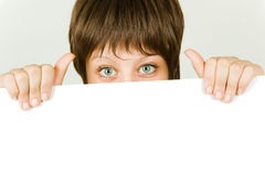 Girl hiding behind a white banner Royalty Free Stock Photography