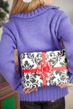Girl Hiding Christmas Gift Behind Back. Rear view of girl hiding Christmas gift behind back at home Stock Photo