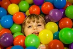 Girl hiding among colorful balls Royalty Free Stock Photography