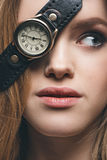 Girl hiding eye with vintage watch. Close-up portrait of blonde fashion girl hiding eye with vintage watch, studio shot Royalty Free Stock Photos