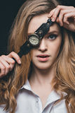 Girl hiding eye with vintage watch. Close-up portrait of blonde fashion girl hiding eye with vintage watch, studio shot Royalty Free Stock Image