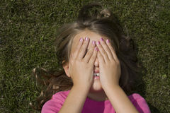 Girl hiding face. A teenage girl lying in the grass, hiding her face behind her hands Stock Photography