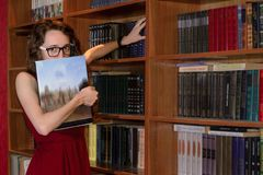 Girl hiding face behind book in library. Beautiful Young woman hiding face behind book looking at camera in a library Royalty Free Stock Photos