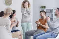 Girl hiding face in hands. Girl hiding her face in her hands and happy people laughing and clapping in group psychotherapy Stock Images