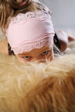 Girl hiding in fur Stock Images