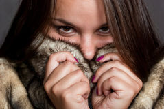 Girl hiding in fur coat Stock Photo