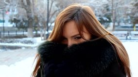 Girl hiding her face in fur coat. Young woman stock video footage