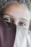 Girl is hiding her face by striped pillow. Royalty Free Stock Images