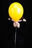 Girl hiding her face under balloon, vertical shot. Girl hiding her face under yellow balloon, vertical studio shot over black background Royalty Free Stock Images