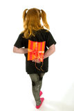 Girl is hiding a present. Red haired girl is hiding a present Royalty Free Stock Photos