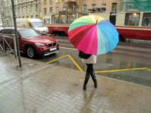 Girl hiding from the rain under an umbrella. She`s waiting at the bus stop stock photos