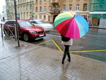 Girl hiding from the rain under an umbrella. She`s waiting at the bus stop royalty free stock image