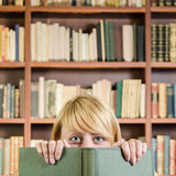 Girl hiding and smiling behind a book - square composition. A shot of girl at library, hiding and smiling behind a book (square composition Royalty Free Stock Image