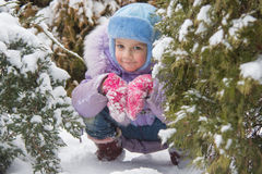 Girl hiding in the snow-covered fur-trees Stock Photo
