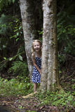 Girl Hiding Between Trees Royalty Free Stock Photography