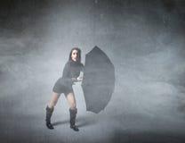 Girl hiding with umbrella Stock Photo