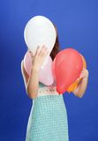 Girl hiding under color balloons Stock Images