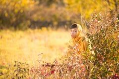 Girl hiding. A girl wearing a yellow hijab hiding behind a bush Stock Photography