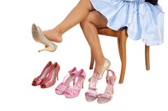 Girl with 4 high heels. A closeup picture of a young woman sitting on a chair for white background Stock Photos
