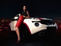 Girl on high heels standing near car Stock Images