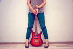 Girl in high heels stands against the wall and holds the electric guitar Stock Photography