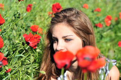 Girl through high poppies Stock Photos