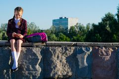 Girl in high school, writes notes outdoors, after school stock photography