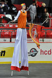 Girl on high stilts with the flag of team Stock Photography