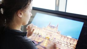 Girl in high tech cafe. Back view young woman moving image and touching on multimedia display close-up portrait and moving hands stock footage