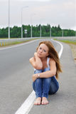 The girl at the highway. Girl sitting on the edge of the road Stock Images