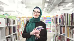 Girl in hijab with books in hands in library. Portrait of a girl in hijab with books in hands looking at camera stock video