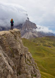 Girl hiker on a clif. Girl hiker standing on a cliff and looking at the mountains Stock Image