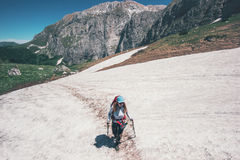 Girl hiker climbing on mountains glacier with backpack Stock Images